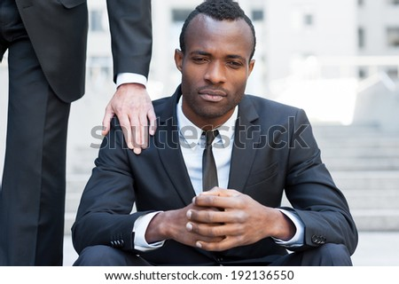 He needs a friendly support. Frustrated young African man in formal wear sitting on staircase while someone touching his shoulder with hand - stock photo