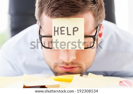 He needs help. Frustrated young man in formal wear with adhesive note on his forehead leaning his head at the table - stock photo