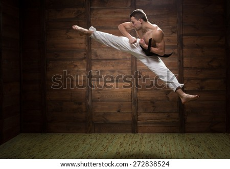 He strong and jumpy. Fighter jumping with foot kick in dojo - stock photo