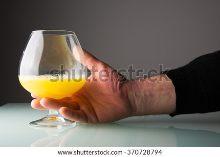 He takes a glass with orange juice