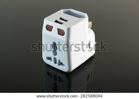he universal adapter on dark reflective background, front focus.