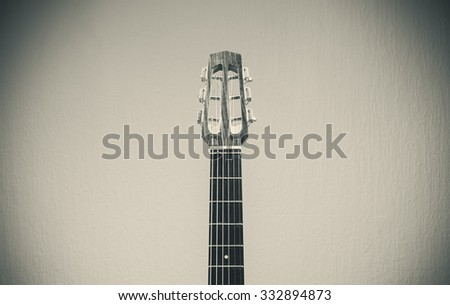Head and neck of an old gypsy guitar in black and white, retro style.
