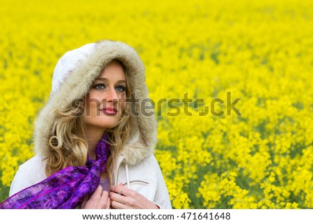 head and shoulder image of a beautiful young woman in a farmland field of canola flowers wearing a white hood