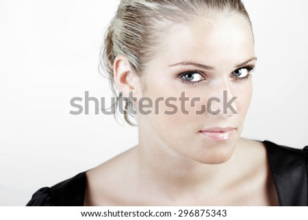 Head and Shoulder Shot of a Gorgeous Young Blond Woman Looking Fierce at the Camera Against White Background.