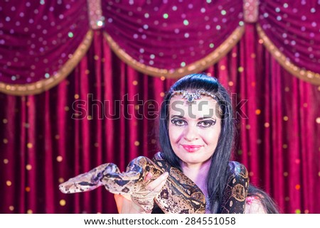 Head and Shoulders Close Up Portrait of Exotic Dark Haired Snake Charmer Wearing Large Snake Around Shoulders on Stage with Red Curtain - stock photo