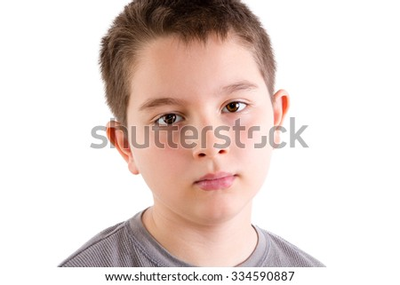 Head and Shoulders Close Up Portrait of Young Boy in Gray T-Shirt Staring at Camera with Blank Expression in Studio with White Background
