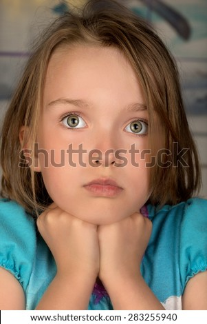 Head and shoulders of a child with pensive expression and hands under her chin - stock photo