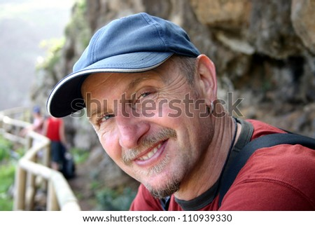 Head and shoulders of male hiker looking sideways into the camera with a baseball hat on