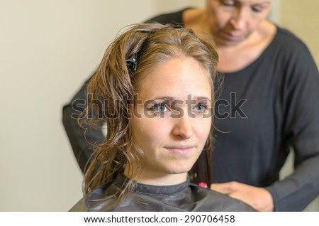 Head and shoulders of pretty smiling serene 20s woman with light brown wet hair clipped up getting hair cut wearing black gown, mid section of hairdresser wearing black top visible in background - stock photo