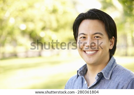 Head and shoulders portrait Asian man outdoors
