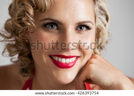 Head and shoulders portrait of a beautiful mid 30s woman dressed with retro vintage hair and makeup