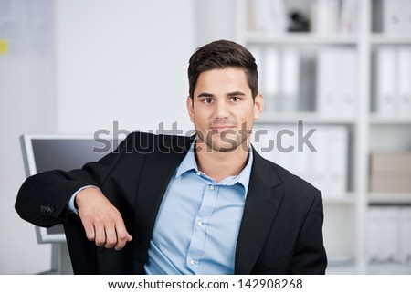 Head and shoulders portrait of a handsome smiling businessman sitting looking directly at the camera in his office - stock photo