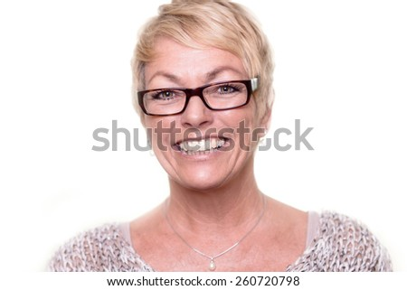 Head and shoulders portrait of a happy attractive middle-aged blond woman wearing glasses looking at the camera with a lovely vivacious smile - stock photo