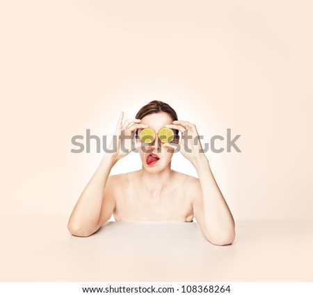 Head and shoulders portrait of a playful woman with sliced rounds of lemon held in front of her eyes and her tongue protruding - stock photo