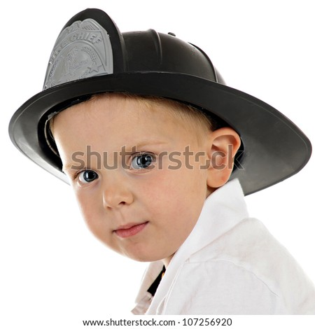 Head and shoulders portrait of a preschooler wearing a fire chief's hat.  On a white background.