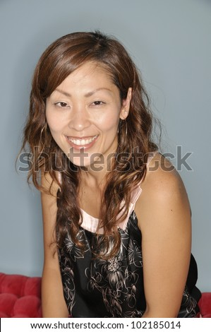 Head and shoulders portrait of a smiling Asian woman in a sleeveless top