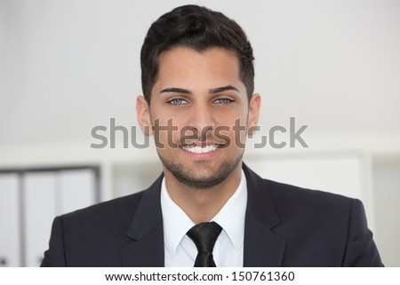 Head and shoulders portrait of a smiling friendly businessman in his office looking directly at the camera - stock photo