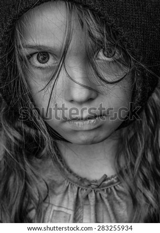 Head and shoulders portrait of a waif like female child (7years old), emotional expression