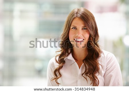 Head and shoulders portrait of a young businesswoman smiling - stock photo