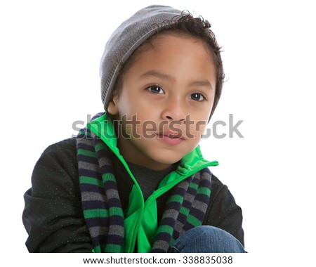Head and shoulders portrait of a young mixed race boy wearing a jacket, scarf and knit hat.  Isolated on white. - stock photo
