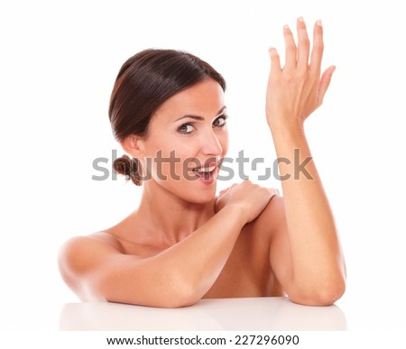 Head and shoulders portrait of charming beautiful woman for body care product showing her freshness with nude shoulders and looking at camera on isolated studio