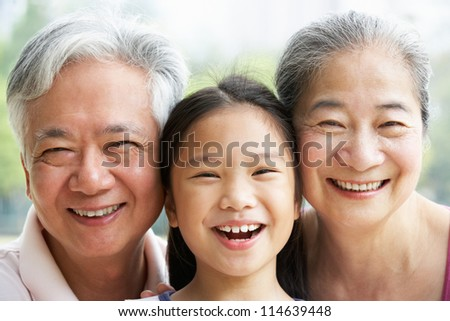 Head And Shoulders Portrait Of Chinese Grandparents With Granddaughter Ride - stock photo