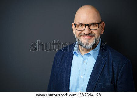 Head and Shoulders Portrait of Mature Man with Facial Hair Wearing Eyeglasses and Dress Shirt with Denim Jacket Smiling Warmly at Camera in Studio with Dark Gray Background and Copy Space - stock photo