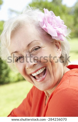 Head And Shoulders Portrait Of Smiling Senior Woman With Flower In Hair - stock photo