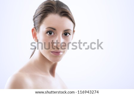 Head and shoulders studio portrait of a beautiful sexy woman with bare shoulders, a natural complexion and her hair tied back in a ponytail looking at the camera with large lustrous eyes
