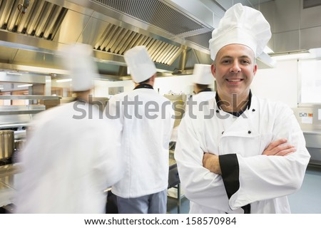 Head chef posing proudly in kitchen with colleagues in the background