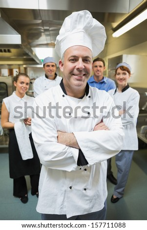 Head chef posing with his team behind him in restaurant kitchen - stock photo