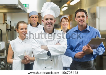 Head chef posing with the team behind him in a professional kitchen - stock photo