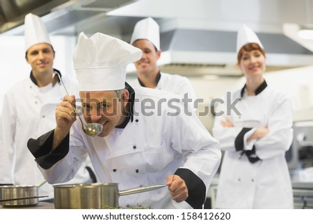 Head chef tasting a soup and smiling at camera while being watched by his colleagues - stock photo