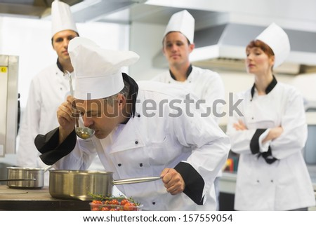 Head chef tasting a soup being watched by his colleagues
