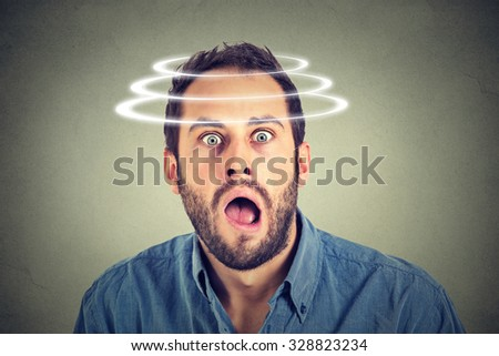 Head is spinning. Surprise astonished man. Closeup portrait man looking surprised in full disbelief wide open mouth isolated on grey wall background. Human emotion face expression body language.
