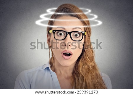Head is spinning. Surprise astonished woman. Closeup portrait woman looking surprised in full disbelief wide open mouth isolated grey wall background. Human emotion face expression body language. - stock photo
