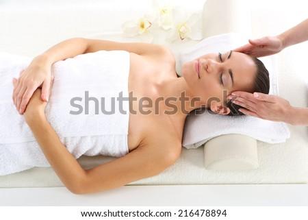 Head massage .Attractive brunette woman in spa salon. - stock photo