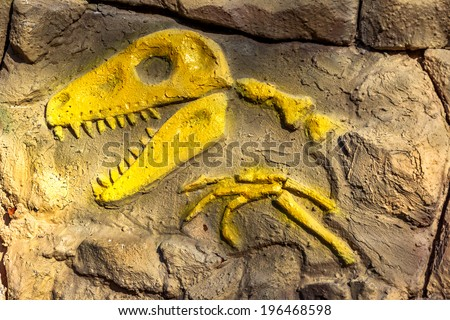 Head model of a prehistoric dinosaur fossils from the Mesozoic era acts boulder wall  - stock photo