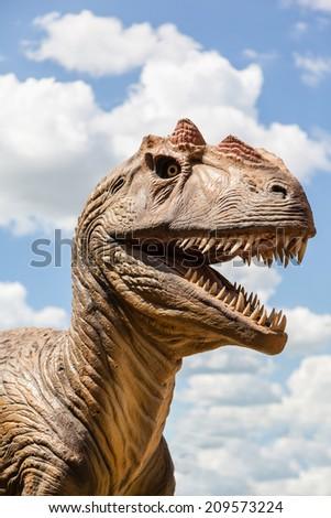 Head of a dinosaur isolated against a blue sky. - stock photo