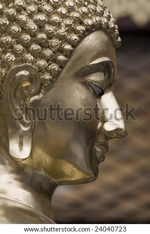 head of a golden buddha in a warm atmosphere - stock photo
