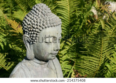 head of a gray buddha-statue in front of fern-green - stock photo