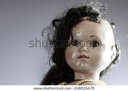 head of beatiful scary doll like from horror movie - evil face, grunge, macro - stock photo