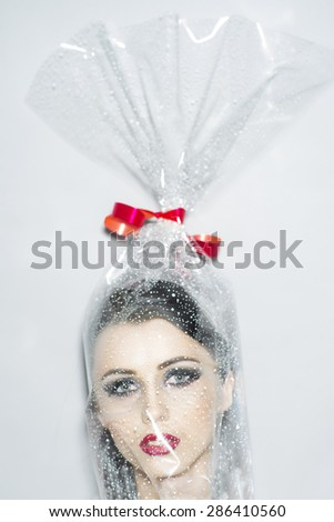 Head of beautiful young brunette woman with bright makeup in cellophane gift wrapping with red bow on white background, vertical picture - stock photo