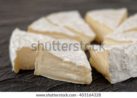 Head of brie cheese cut in pieces on wooden board - stock photo