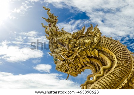 Head of golden giant snake with blue sky background.