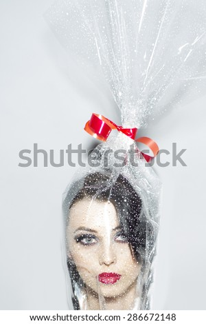 Head of pretty young brunette woman with bright makeup in cellophane present packing with red bow on white background, vertical picture - stock photo