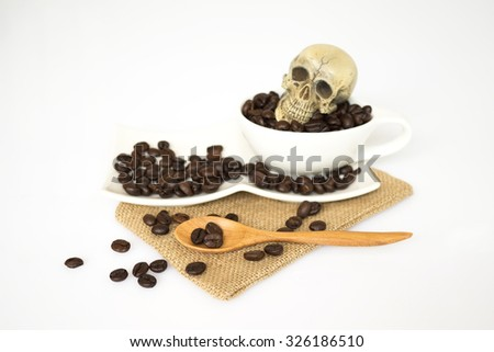 head of skull on the cup of coffee. focus coffee beans on the wood spoon - stock photo