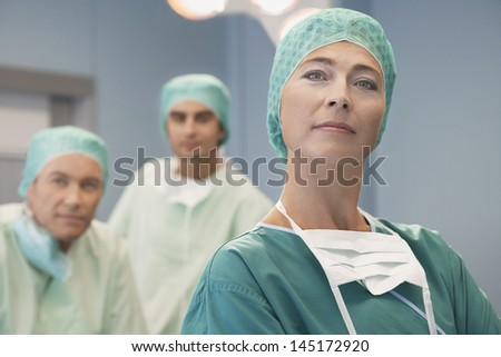 Head of surgical team with surgeons in operating theatre
