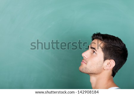 Head profile portrait of a thoughtful young male student in front of a green blackboard looking up towards copyspace on the board - stock photo