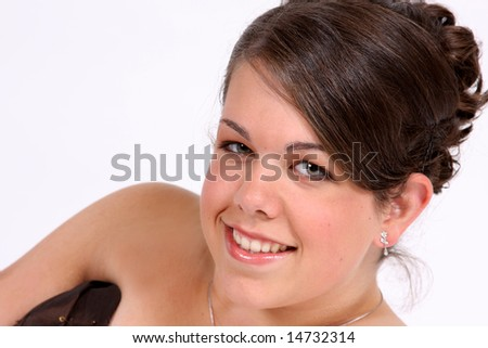 Head shot of a beautiful young woman smiling with hair and makeup done. - stock photo